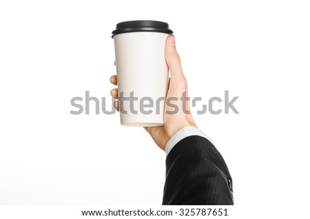 Business lunches coffee theme: businessman in a black suit holding a white blank paper cup of coffee with a brown plastic cap isolated on a white background in the studio, advertising coffee - stock photo