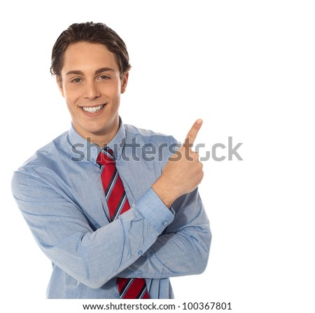 Business male pointing upwards and smiling at camera - stock photo