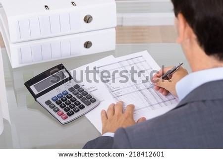 Business man accountant calculating invoices in office - stock photo