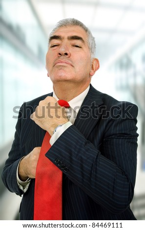 business man adjusting his tie at the office
