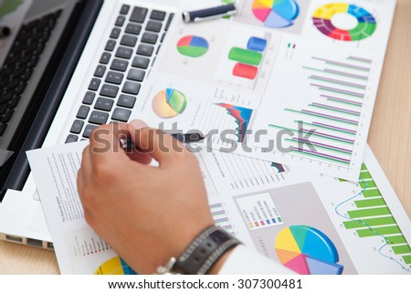 Business man analyzing financial statistics sitting at office desk using smart phone calculator - stock photo