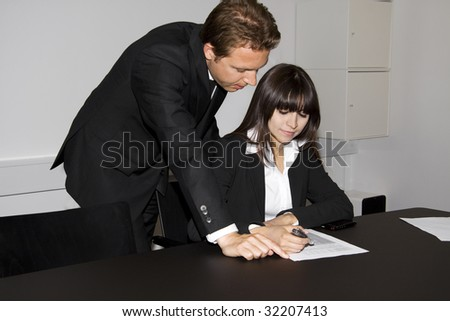 Business man and a business woman is going over a contract together. He is pointing at the paper