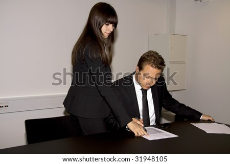 Business man and a business woman is going over a contract together. She is pointing at the paper