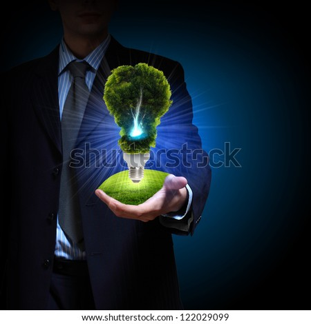 Business man and a light bulb as a symbol of green energy - stock photo