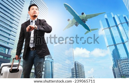 business man and belonging luggage watching to sky and hand watch against high building skyscrapers and passenger plane flying above use for aircraft ,air transportation ,traveling of people theme  - stock photo