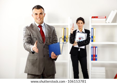 Business man and business women in the office hi is ready for a handshake while she is behind him with some charts - stock photo