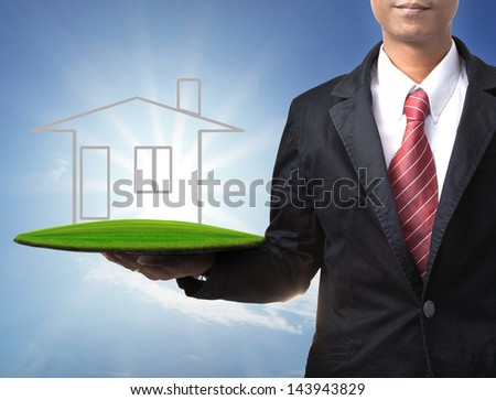 business man and home on green land in hand for multipurpose