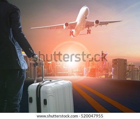 business man and traveling luggage standing against skyline and passenger plane taking over airport runway