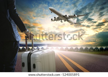 business man and traveling luggage standing in airport terminal and passenger plane flying over sky