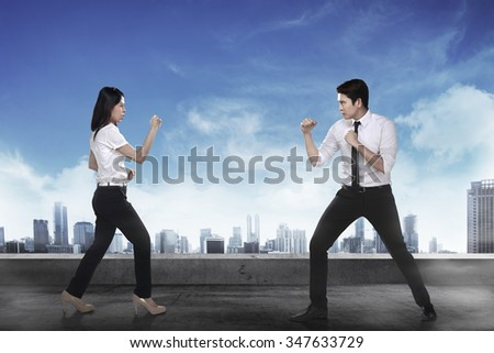 Business man and woman fighting. Working competition concept