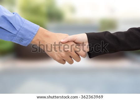 Business man and woman handshake on blur background concept