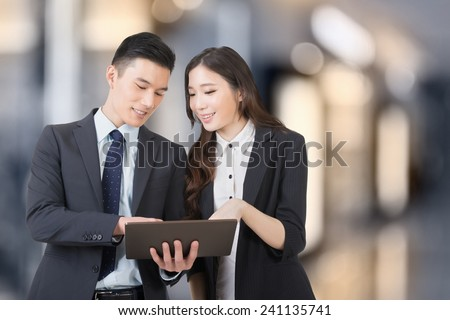 Business man and woman hold a tablet and discuss, closeup portrait with copyspace. - stock photo