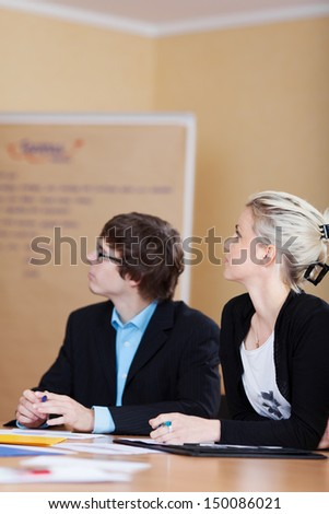 Business man and woman in a seminar sitting at a table looking off to the side towards a flipchart - stock photo