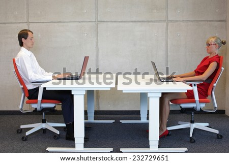 business man and woman in correct sitting posture at workstations in the office - stock photo