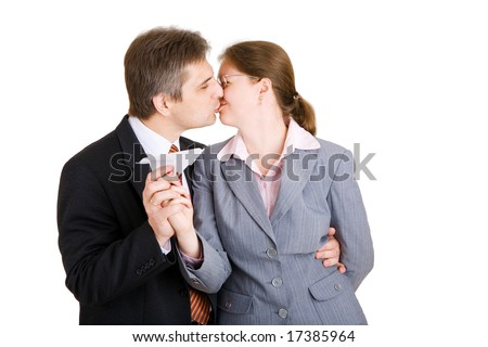 business man and woman kiss with paper airplane in hands - stock photo