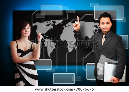 Business man and woman look at the world map on black LED screen monitor