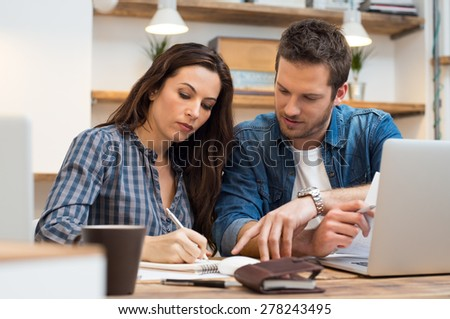 Business man and woman making note in office