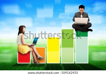 Business man and woman on Bar graph on the grass field - stock photo