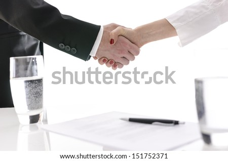 Business man and woman shaking hands after signing a contract. Isolated over white background.
