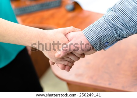 Business man and woman shaking hands closeup image in office - stock photo