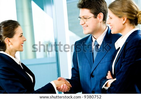Business man and woman shaking hands making an agreement at meeting - stock photo