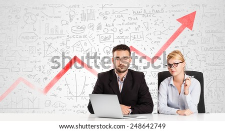Business man and woman sitting at table with market hand drawn diagrams  - stock photo