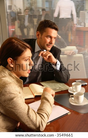 Business man and woman sitting at the desk in the office and having meeting - stock photo
