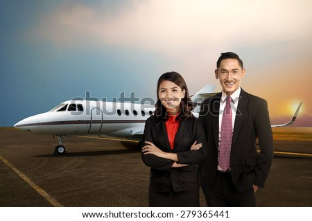 Business man and woman smiling in front of private jet. Business travel concept - stock photo