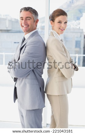Business man and woman smiling standing back to back - stock photo