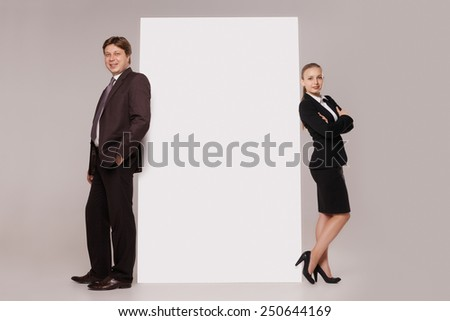 Business man and woman standing back to back on both sides of blank banner  isolated on grey background. Teamwork concept - stock photo