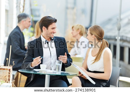 Business man and woman talking outdoors in a coffee shop with each other - stock photo