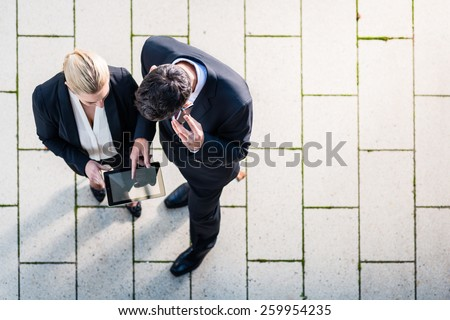Business man and woman  with tablet computer standing on square, seen in top view - stock photo