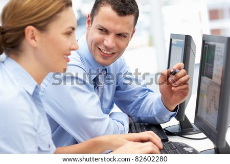 Business man and woman working on computers - stock photo