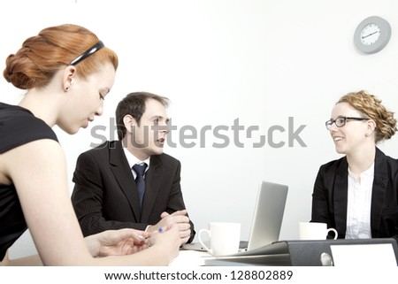Business man and women having a meeting grouped around a table and laptop in an office discussing their plans and strategy as a team