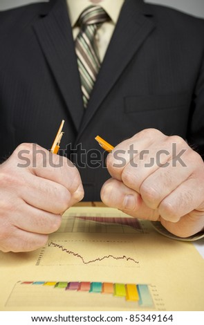 Business man angry over financial loses breaks a pencil in half