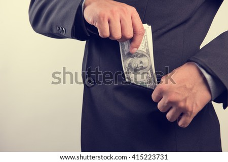 Business man are keeping money in pocket, US dollar (USD) bills - investment, success and profitable business concepts - stock photo