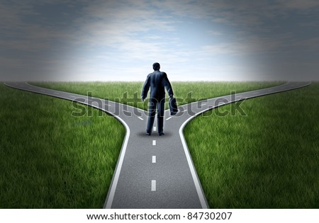 Business man at a cross roads standing at a fork in the road representing the concept of a strategic dilemma choosing the right direction to go when facing two equal or similar options. - stock photo
