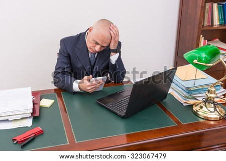 business man at desk, contemplating your i pad/tablet, in his professional office.