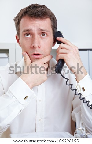Business man at desk in office thinking on phone - stock photo