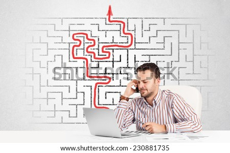 Business man at desk with labyrinth in the background - stock photo