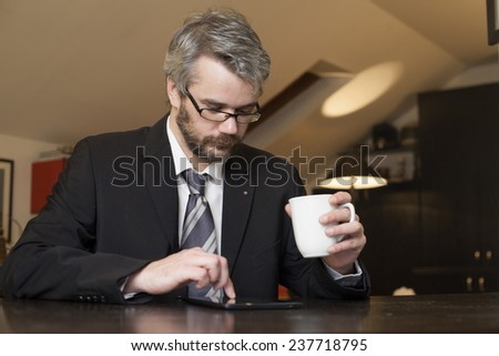 Business Man At Home Using A Laptop Computer And Drinking Coffee