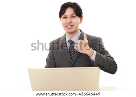 Business man at laptop, shows thumb up sign