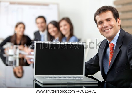 Business man at the office with a laptop smiling