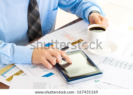 business man at workplace with tablet pc and drink coffee - stock photo