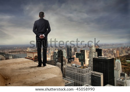 business man back on a skyscraper - stock photo