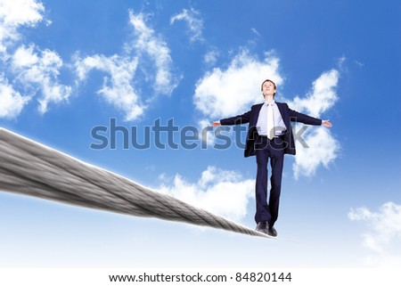Business man balancing on the rope high in the sky - stock photo