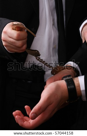 business man being arrested, only the hands of the police detective and business man are visible - stock photo