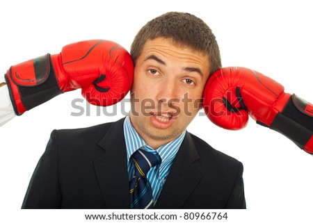 Business man being kicked by two boxing gloves and making a face isolated on white background