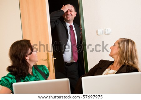 Business man being late from meeting, three women looking at him - stock photo