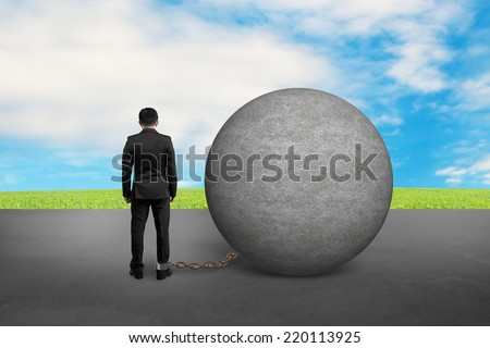 business man being trapped with concrete ball and nature sky - stock photo